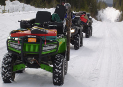 Line of ATVs on a snowy trail